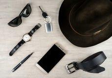 Smartphone, odczuwani mężczyzna ` s akcesoria na powierzchni, kapeluszowi i inni obraz stock