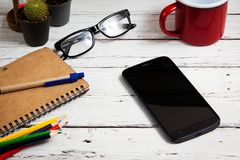 Smartphone and office supplies on tabel, top view.  Royalty Free Stock Photos