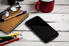 Smartphone and office supplies on tabel, top view.  Stock Photos