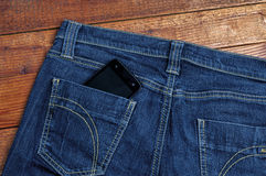Smartphone in the old jeans. Pocket on wood background Stock Images