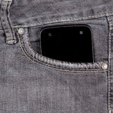 Smartphone in the old jeans. Pocket on wood background Stock Photo