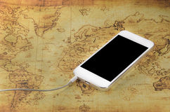 Smartphone on a old world map Royalty Free Stock Photography