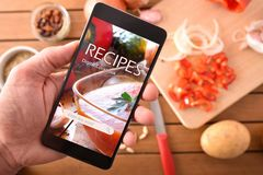 Using digital cookbook app in smartphone for cooking closeup stock photography