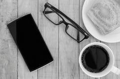 Smartphone, oogglazen en koffie op houten patroonachtergrond die wordt geplaatst royalty-vrije stock afbeeldingen