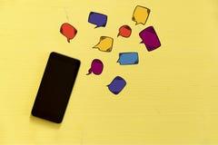 Smartphone op gele achtergrond met tekst rond bellen Messag Royalty-vrije Stock Afbeeldingen