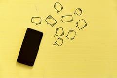 Smartphone op gele achtergrond met tekst rond bellen Messag Stock Foto's