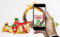Smartphone op hand met `-VERKOOP ` op het scherm, met Kerstmisdecoratie siert, de Verkoop van Vakantiekerstmis Stock Fotografie