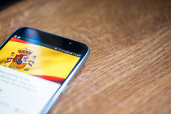 Smartphone op houten achtergrond met 5G netwerkteken 25 percentenlast en Spanje markeert op het scherm royalty-vrije stock foto's