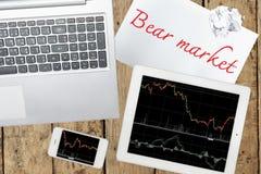 Smartphone, ordenador, tableta con el gráfico y papel con la marca del oso Fotos de archivo