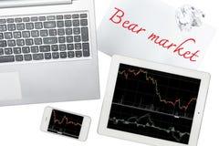 Smartphone, ordenador, tableta con el gráfico y papel con la marca del oso Imagenes de archivo