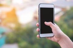 Smartphone ou téléphone portable de participation de main avec le fond de bâtiment de ville et l'espace de copie photos stock