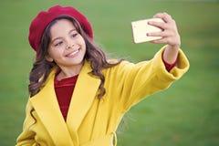 Smartphone ou t?l?phone portable de prise de petite fille Communication moderne de g?n?ration Concept de communication mobile Enf image libre de droits