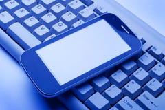 Smartphone på datoren skrivar royaltyfri fotografi