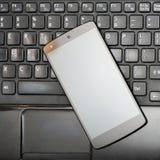 Smartphone på det svarta bärbar datortangentbordet Fotografering för Bildbyråer