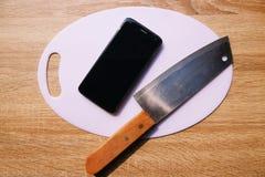 Smartphone på slaktare och kniven royaltyfri foto