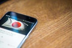 Smartphone på träbakgrund med tecknet för nätverket 5G 25 procent laddning och Japan sjunker på skärmen Royaltyfri Bild