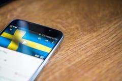 Smartphone på träbakgrund med tecknet för nätverket 5G 25 procent laddning och Sverige sjunker på skärmen Arkivfoton