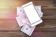 Smartphone, pacchetti dei dollari su un fondo di legno della tavola fotografia stock