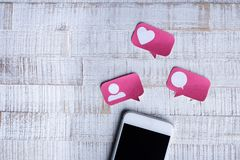 Smartphone with Paper Cut Social Media Icons in Speech Bubble. On Wooden Background stock images