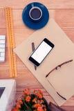 Smartphone par des verres d'oeil sur le papier par la tasse de café au bureau Photos libres de droits