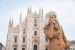 Smartphone parlant de femme heureuse tout en tenant le Duomo proche, Milan Image stock