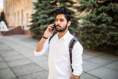 Smartphone parlant de jeune étudiant indien beau dans la rue de ville images libres de droits