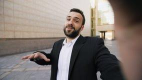 Smartphone parlant de jeune homme d'affaires barbu ayant la réunion d'affaires visuelle en ligne de causerie dehors photo libre de droits
