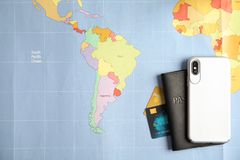 Smartphone, passport and credit cards on world map. Travel agency. Smartphone, passport and credit cards on world map, top view. Travel agency stock photo