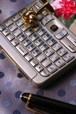 Smartphone PDA On Silk Tie. Smartphone PDA, pen and gold cufflink sitting on a gray silk tie stock photography