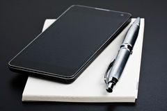 Smartphone and Pen on Memo Book Royalty Free Stock Photo