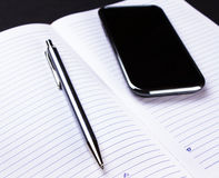 Smartphone, pen and notebook on black Stock Photography