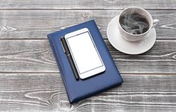 Smartphone with a pen on a notebook. Of blue color, a cup of coffee on a wooden table background Stock Photo