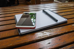 Smartphone and pen put on empty notebook on wood. Background Royalty Free Stock Photo