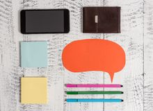 Smartphone phone pens ballpoints blank colored speech bubble sticky notes leather wallet lying wooden rustic vintage. Smartphone pens blank speech bubble sticky royalty free stock image