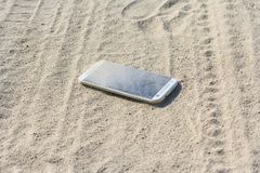 Smartphone a perdu dans le sable Image stock