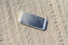 Smartphone a perdu dans le sable Images stock