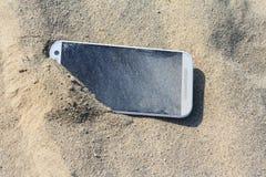 Smartphone a perdu dans le sable Image libre de droits