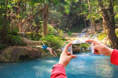 Smartphone photographing Asian young man jumping in the Erawan waterfall stock image