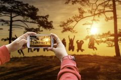 Smartphone photographing asians traveler jumping in happy time at Phu Kradueng National Park at Sunset in Loei Province. Of thailand stock photo
