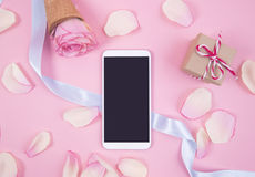 Smartphone with pink petals on pastel background Stock Image