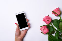 Smartphone and pink roses on a white background. Stock Photo