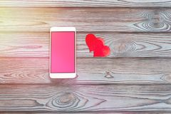 Smartphone with a pink screen. A heart shaped figure on a wooden table background Royalty Free Stock Images