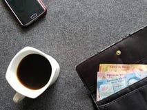 smartphone, plånbok för kvinna med mexikanska sedlar och kaffekopp på den gråa tabellen fotografering för bildbyråer