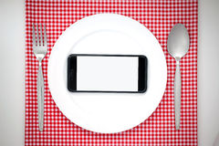 Smartphone on plate. Smartphone on white dish or plate between spoon, fork on red classic checkered tablecloth texture on white table with copy space for royalty free stock image
