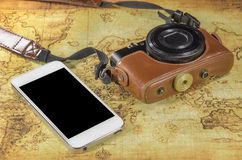 Smartphone and pocket camera on a world map Stock Photos
