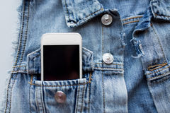 Smartphone in pocket of denim jacket or waistcoat Royalty Free Stock Images