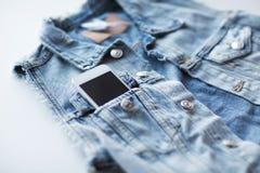 Smartphone in pocket of denim jacket or waistcoat Stock Photo