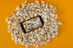 Smartphone and popcorn on yellow table. Technology concept. cinema on a smartphone with background of popcorn stock image