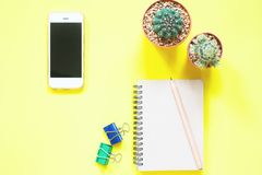Smartphone with pot of cactus and stationery on yellow background, Overhead view Royalty Free Stock Photos
