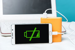 A smartphone with the power bank in the foreground of the camera. Royalty Free Stock Image